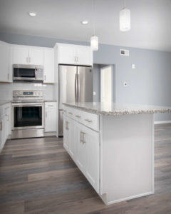 Front of island CNC Luxor cabinets in White in the kitchens at Residences On Main in Bristol.